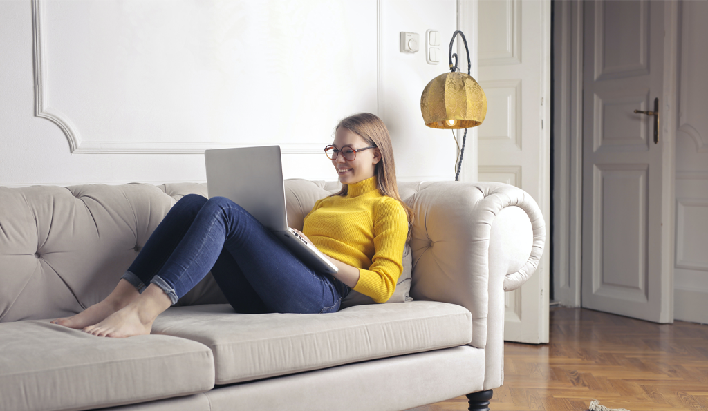 woman sitting on couch using laptop inside condo